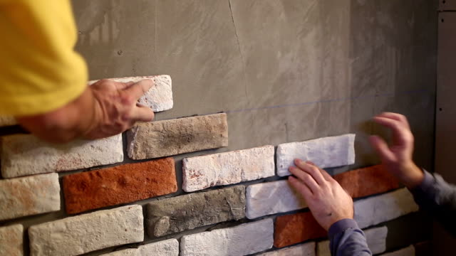 workers putting tiles on a wall , sticking brick plates on a wall