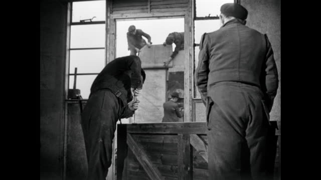 stockvideo's en b-roll-footage met montage workers rebuilding a home and working on roofs and windows / england, united kingdom - 1946