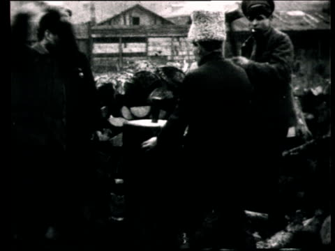 vidéos et rushes de 1921 montage b/w ws workers rebuilding steel bridge after russian civil war/ ms men splitting wood logs/ ms mikhail kalinin visiting building site/ ms pan workers stacking wood logs/ ms kalinin meeting workers and helping to cut logs/ russia - chemin de fer