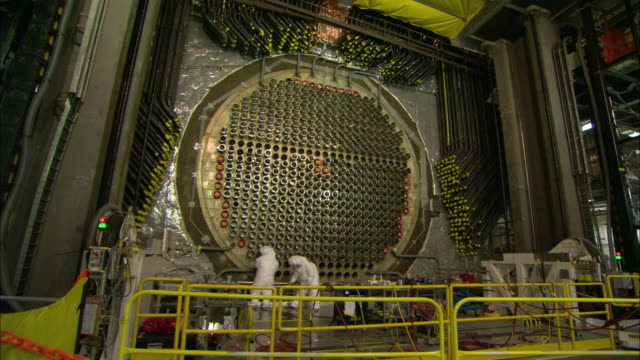 stockvideo's en b-roll-footage met workers refurbish tube channels on a nuclear reactor panel. - energie industrie