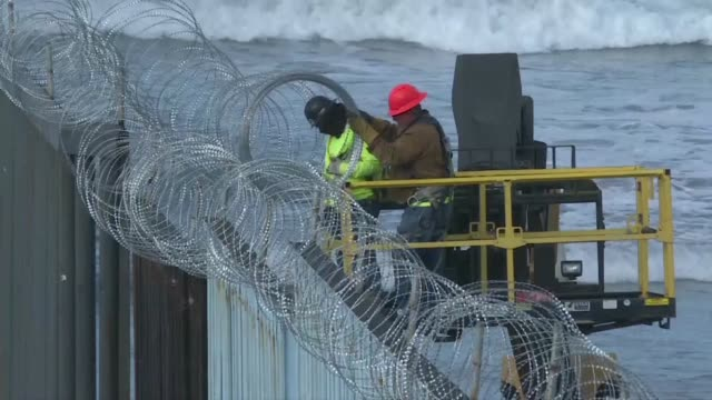 stockvideo's en b-roll-footage met us workers reinforce the tijuana san diego border wall by placing barbed wire on the american side of a beach separating it from the mexican town - san diego