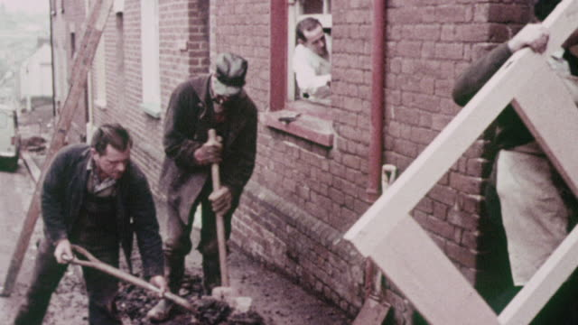 montage workers remodeling row house exterior and digging up street / exeter, england, united kingdom - terraced house stock videos & royalty-free footage