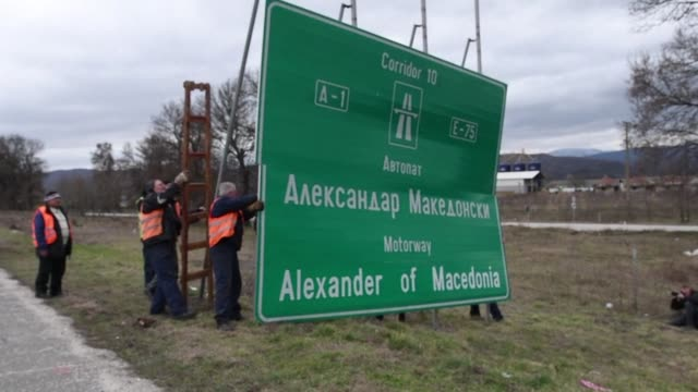 Workers remove a sign with the former name of the highway leading to the Greek border Alexander of Macedonia newly renamed Friendship Highway near...