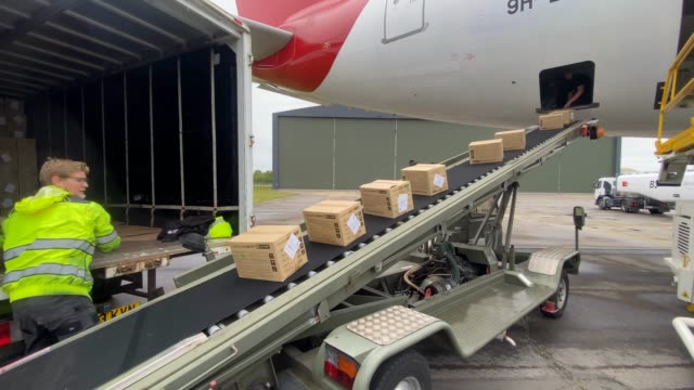 workers remove boxes of ppe supplies from a conveyer belt out of the nhs branded plane that arrived from kuala lumpur malaysia on the runway at... - belt stock videos & royalty-free footage