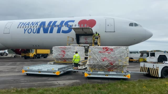 workers remove boxes of ppe supplies from the nhs branded plane that arrived from kuala lumpur, malaysia on the runway at bournemouth airport during... - politik und regierung stock-videos und b-roll-filmmaterial
