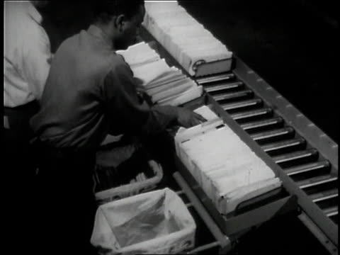 1957 ms workers removing mail trays from conveyor line / united states - united states postal service stock videos & royalty-free footage