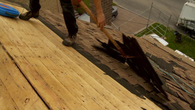 Workers removing old shingles from roof