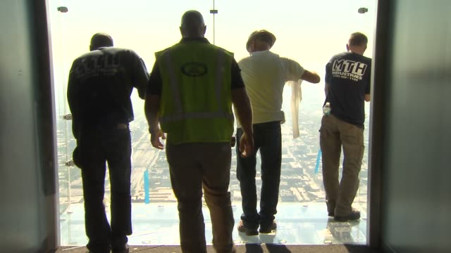 workers replaced the glass in standing area of the transparent observation deck ledge in the willis tower skydeck on may 29 2014 in chicago illinois - willis tower stock videos & royalty-free footage