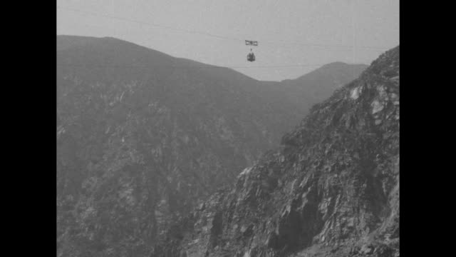 workers ride cage suspended from wires over gorge during pacoima dam construction / cage as it moves across wires over rocky area of the san gabriel... - tall high stock videos & royalty-free footage