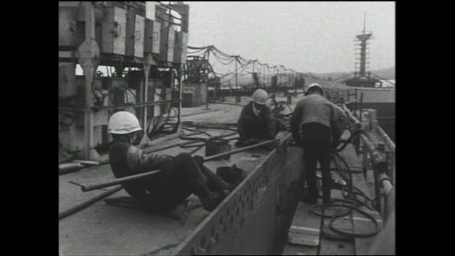 workers rivet bulkhead sections on a cargo ship under construction in a shipyard at the port of osaka. - showa period stock videos & royalty-free footage