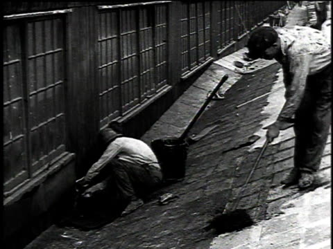 1921 montage workers roofing a factory roof with hot asphalt, tar, and sheets of asbestos felt / united states - アスベスト点の映像素材/bロール