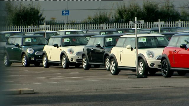 workers sacked without warning from oxford mini car factory; england: oxford: cowley: ext good shots new mini cooper cars parked in car park of... - オックスフォードシャー点の映像素材/bロール