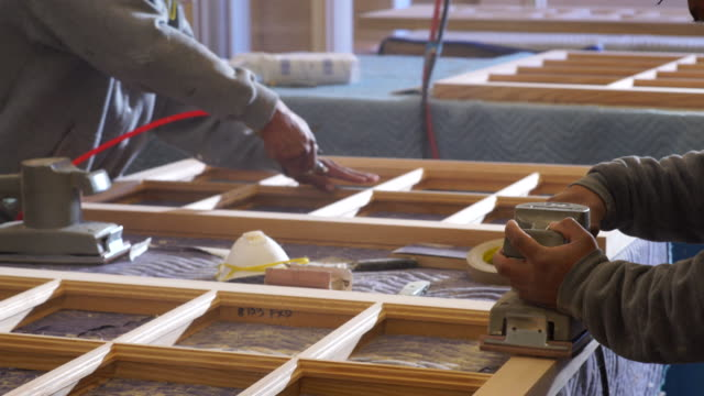 Workers sand custom window frames in woodworking shop