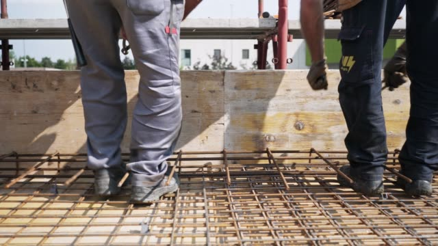 vídeos de stock e filmes b-roll de workers securing metal frames with wire, to keep them in place, and ready for concrete pour - maquinaria de fabrico