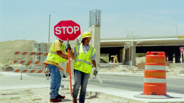 MS, PAN, workers setting up barricade while female worker holds stop sign at building site, San Antonio, Texas, USA