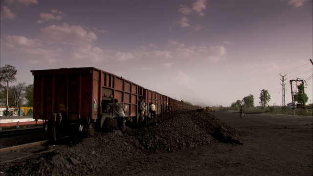 workers shovel coal from freight-train wagons. - 石炭点の映像素材/bロール