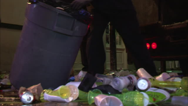 workers shovel trash at night on bourbon street. - bottiglia video stock e b–roll