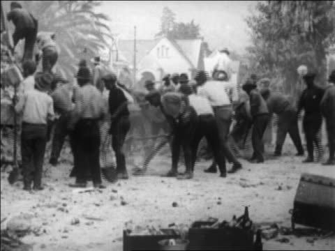 workers shoveling debris after earthquake / santa barbara, ca / newsreel - anno 1925 video stock e b–roll