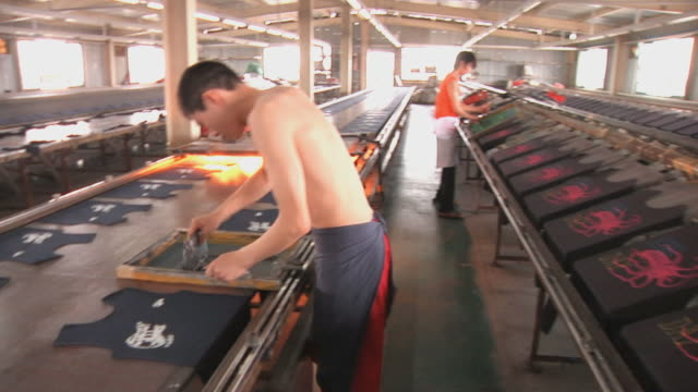 stockvideo's en b-roll-footage met ws workers silk-screening t-shirts in factory / ningbo, zhejiang, china - ningbo