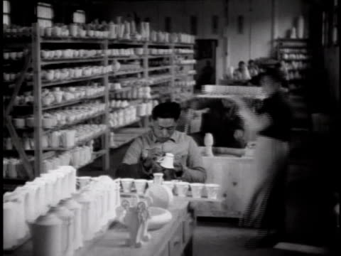 stockvideo's en b-roll-footage met 1944 ws workers sitting at work benches making tea cups at a porcelain plant, other workers carrying trays in the background / china - communisme