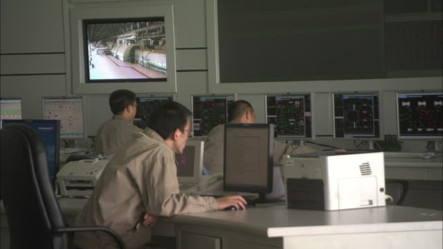 MS Workers sitting behind row of computer screens in control room at Huaneng Yuhuan power plant, Yuhuan County, Zhejiang, China