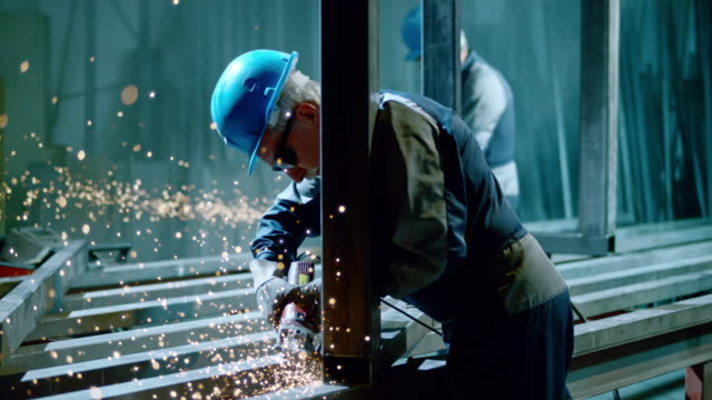 vidéos et rushes de slo mo ds workers smoothening weld on metal frame - structure bâtie
