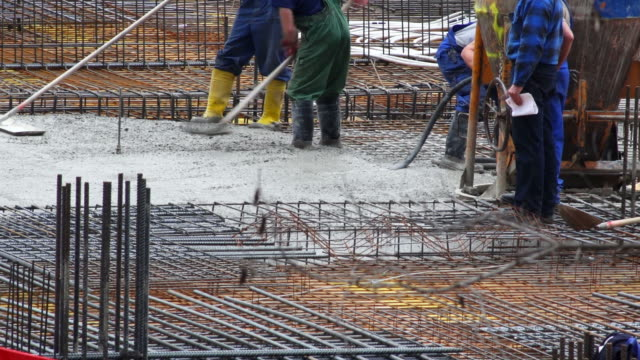 workers smoothing concrete on construction site - baugewerbe stock videos & royalty-free footage