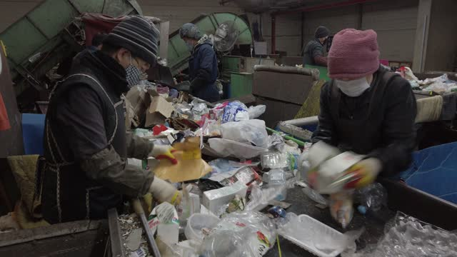 workers sort of household waste moving along a conveyor at a facility that stores recyclable materials following the lunar new year's holiday on... - capodanno coreano video stock e b–roll