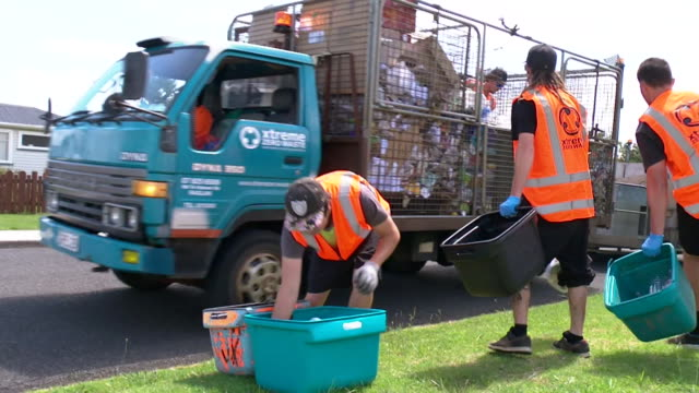 Workers sorting plastic and metal recyling waste from bins and emptying waste into back of truck