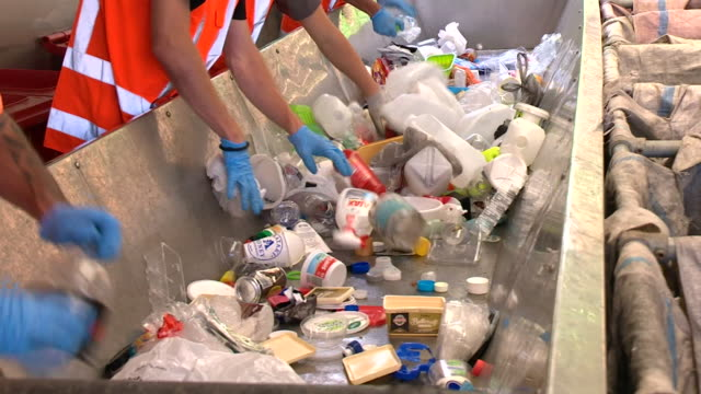 Workers sorting plastics in large bin at recycling centre