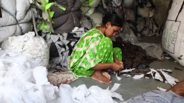 workers sorting through garment leftovers at a jhoot godown in dhaka. recycling of waste raw materials left by garment factories has emerged as a... - textile industry stock videos & royalty-free footage