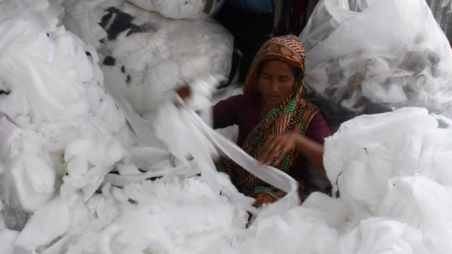 workers sorting through garment leftovers at a jhoot godown in dhaka recycling of waste raw materials left by garment factories has emerged as a good... - leftovers stock videos & royalty-free footage