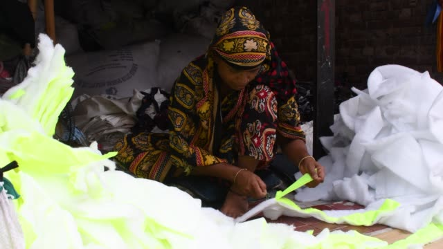 workers sorting through garment leftovers at a jhoot godown in dhaka. recycling of waste raw materials left by garment factories has emerged as a... - garment stock videos & royalty-free footage