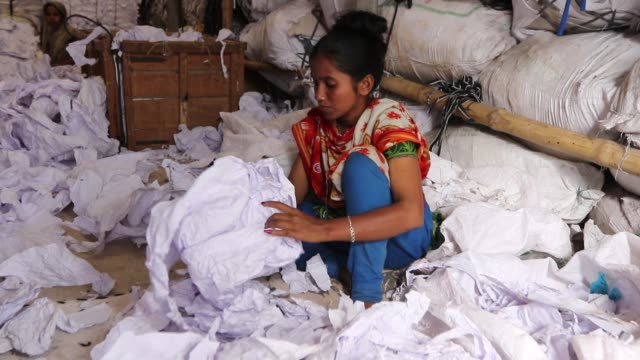 stockvideo's en b-roll-footage met workers sorting through garment leftovers at a jhoot godown in savar near dhaka recycling of waste raw materials left by garment factories has... - kledingstuk
