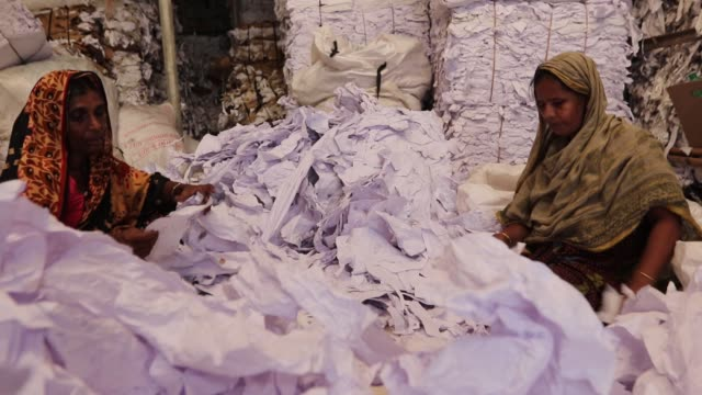 workers sorting through garment leftovers at a jhoot godown in savar near dhaka recycling of waste raw materials left by garment factories has... - leftovers stock videos & royalty-free footage