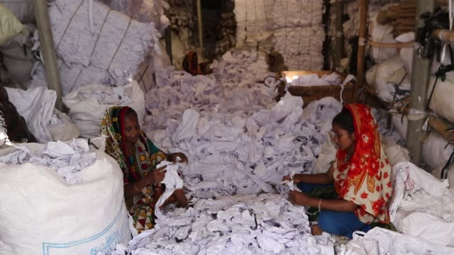 workers sorting through garment leftovers at a jhoot godown in savar near dhaka. recycling of waste raw materials left by garment factories has... - textile industry stock videos & royalty-free footage