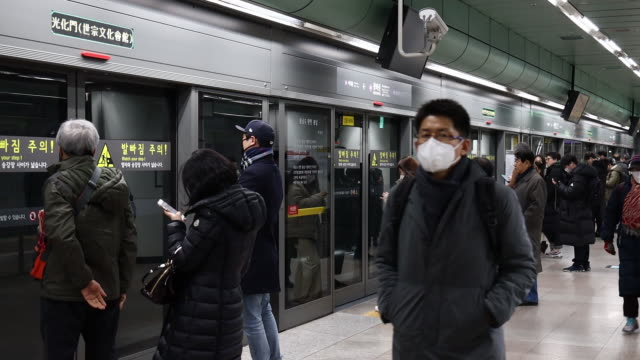 workers spray disinfectant inside the gwanghwamun subway station and people in surgical masks amid the coronavirus crisis in seoul south korea on... - seoul stock videos & royalty-free footage