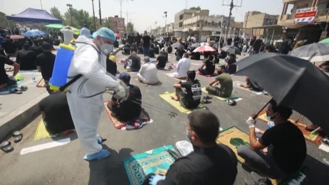 workers spray supporters of shiite cleric moqtada al-sadr with disinfectant, as they take part in the friday prayers in sadr city, east of the iraqi... - iraq video stock e b–roll