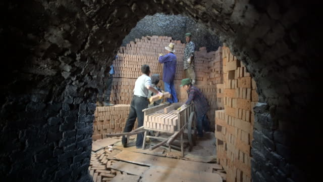 workers stack red bricks in traditional brick kilns ready to be burned - industrie ofen stock-videos und b-roll-filmmaterial