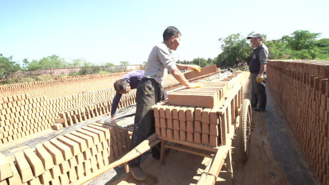 vidéos et rushes de workers stack red bricks in traditional brick kilns ready to be burned - brique