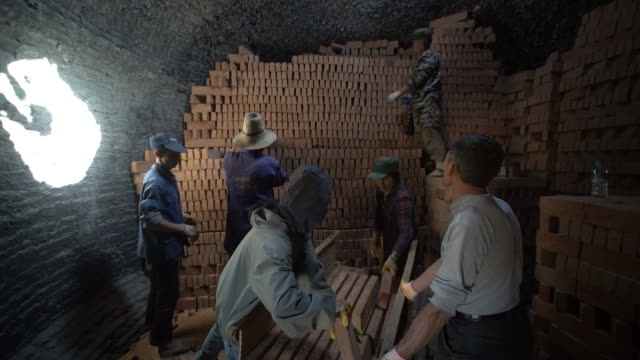 workers stack red bricks in traditional brick kilns ready to be burned - pottery stock videos & royalty-free footage