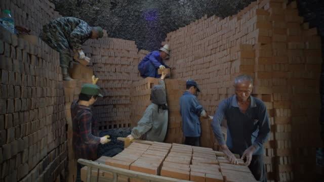 stockvideo's en b-roll-footage met workers stack red bricks in traditional brick kilns ready to be burned - schoorsteen