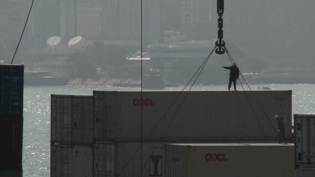 Workers stand on shipping containers and guide crane on dock, Hong Kong