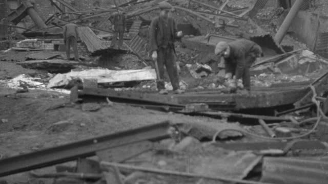 stockvideo's en b-roll-footage met montage workers standing on rubble, and digging for coal lumps in piled dirt and debris / treforest, wales, united kingdom - grote depressie nieuwsevenement