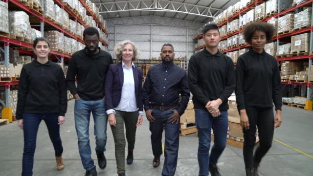 vidéos et rushes de travailleurs debout avec les bras croisés en entrepôt - collègue