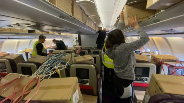stockvideo's en b-roll-footage met workers start to gather the boxes strapped to the chairs and stowed above of ppe supplies inside the plane arriving from kuala lumpur, malaysia on... - start  en landingsbaan