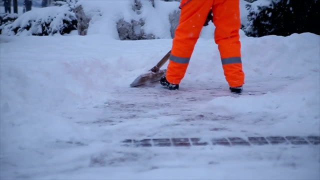 workers sweep snow from road in winter. cleaning city from snow storm - snowplough stock videos & royalty-free footage