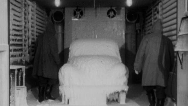 1952 b/w workers take a frozen morris minor out of a freezer for testing / united kingdom - 1952 個影片檔及 b 捲影像