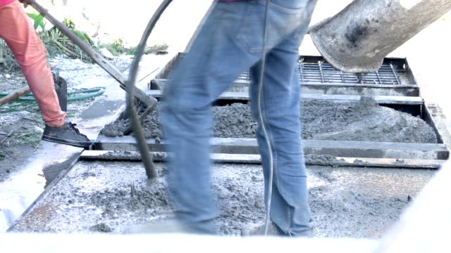 Workers take concrete from a mixer into formwork.