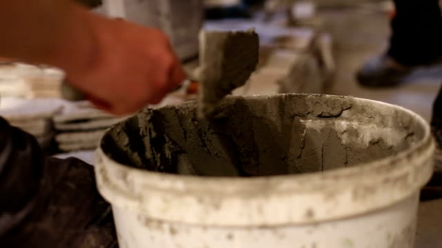 workers taking cement with a spatula  from a bucket - construction material stock videos and b-roll footage